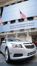 Passersby look on as General Motors' vehicles are displayed in front of the New York Stock Exchange on the morning of GM's initial public offering Thursday, November 18, 2010 in New York. 11/18/2010