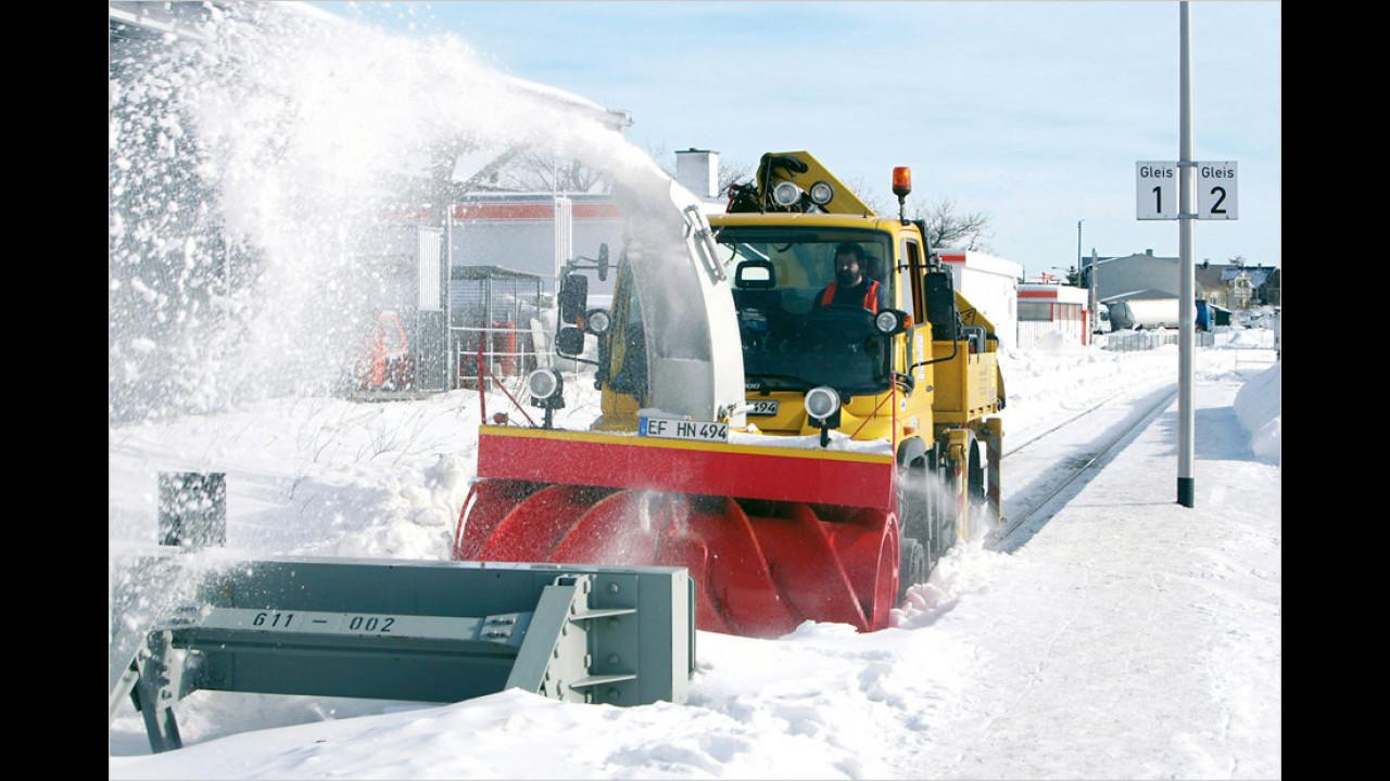 2-Wege-Unimog beim Schneeräumen auf der Schiene